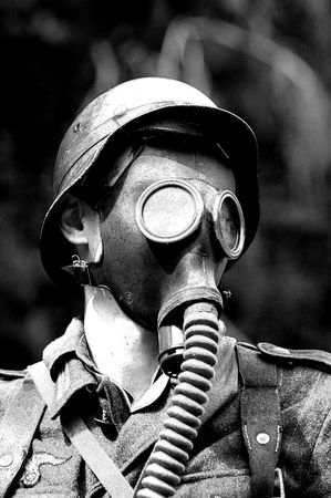 vintage military rifle: German soldier in gas mask.WW2 historical reenactment