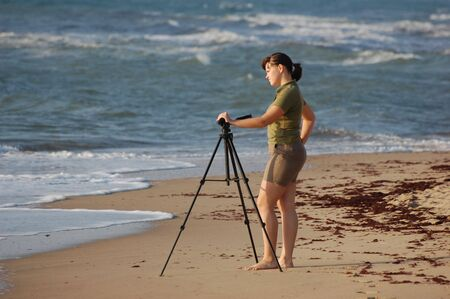 Photographer girl setting up tripod near the sea. Black Sea coast near Odessa,Ukraine  photo