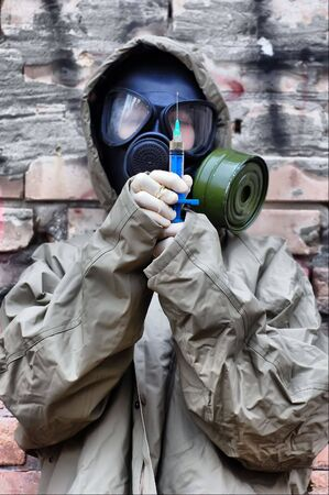 HDR. Person in gas mask with syringe  photo
