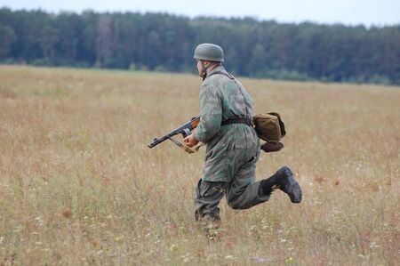 wears: CHERNIGOW, UKRAINE - AUG 29: A member of Red Star military history club wears historical German paratrooper uniform during historical reenactment of WWII, August 29, 2010 in Chernigow, Ukraine  Editorial