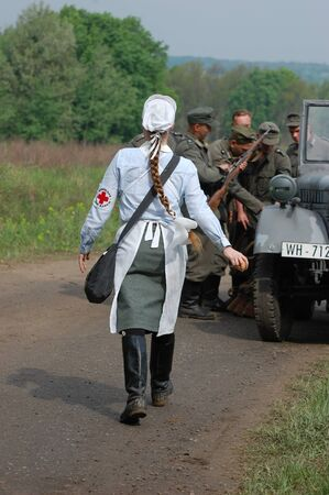 military invasion: KIEV, UKRAINE - MAY 10 : member of Red Star history club wears historical military German paramedic uniform during historical reenactment of 1945 WWII, May 10, 2010 in Kiev, Ukraine
