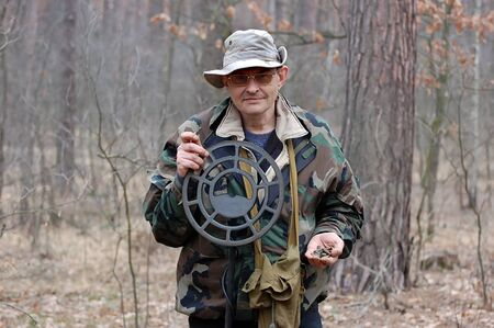 Military archeology. Man with metal detector and excavated Soviet cartridges 5,45 mm caliber on the battlefield of WW2.Ukraine Stock Photo - 9091631