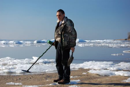 archeologist: Military archeology. Man with metal detector on the battlefield of WW2.Ukraine