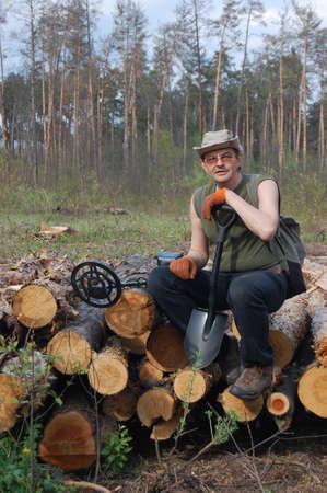 scavenge: Military archeology. Man with metal detector on the battlefield of WW2.Near Kiev,Ukraine