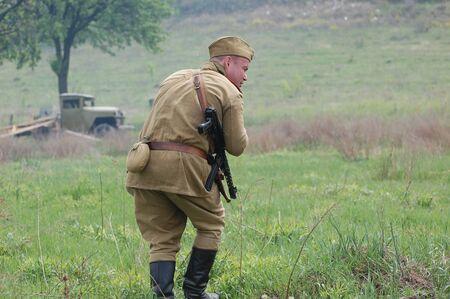 re enacting: KIEV, UKRAINE - MAY 8 : A member of Red Star history club wears historical Soviet uniform during historical reenactment of WWII on May 8, 2011 in Kiev, Ukraine  Editorial