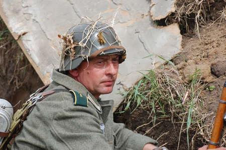 re enacting: KIEV, UKRAINE - MAY 8 : An unidentified member of Red Star history club wears historical German uniform during historical reenactment of WWII on May 8, 2011 in Kiev, Ukraine  Editorial