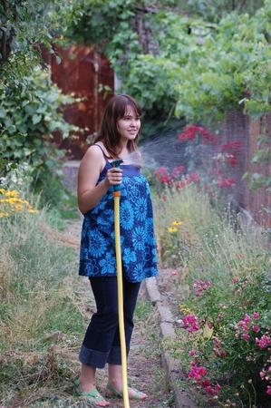 Beautiful young  girl watering garden near Kiev,Ukraine photo