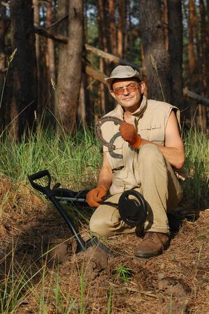 Military archeology. Man with metal detector and German WWII time horse-shoe. Eastern Europe.White ballans of sunset time Stock Photo - 10182036
