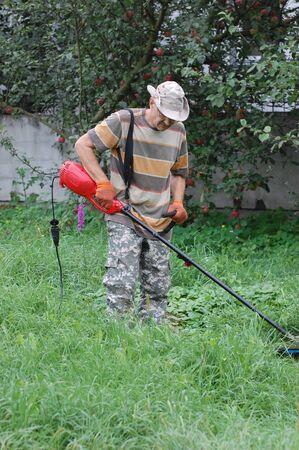 Man mowing grass.Ukraine photo