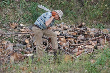 machete: Man with machete chop logs for firewood.Ukraine  Stock Photo