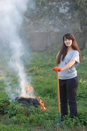 cute young farm girl: Teen girl burn out dry grass in the garden.Ukraine  Stock Photo