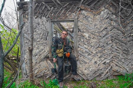 archeologist: Man with metal detector in the abandoned village. Ukraine