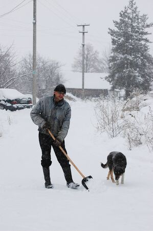 Adult man clean owns road to home  against snow.Near Kiev,Ukraine Stock Photo - 12076186