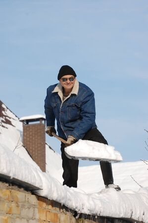 A man with a shovel removing snow from a roof . Near Kiev,Ukraine  photo