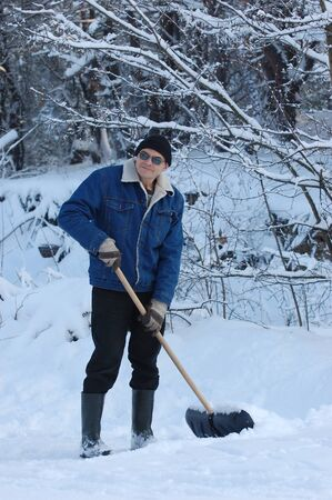 Adult man clean owns road to home against snow.Near Kiev,Ukraine  photo