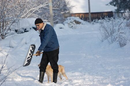 Adult man clean owns road to home against snow.Near Kiev,Ukraine Stock Photo - 12076197