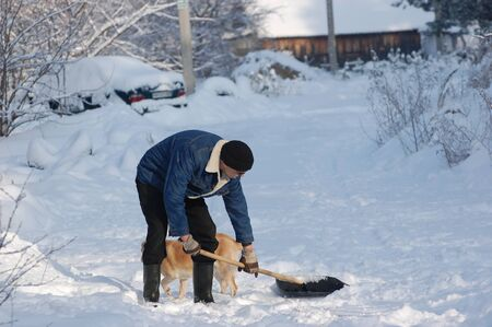 Adult man clean owns road to home against snow.Near Kiev,Ukraine Stock Photo - 12076195