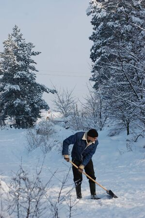 Adult man clean owns road to home against snow.Near Kiev,Ukraine  Stock Photo - 12076203