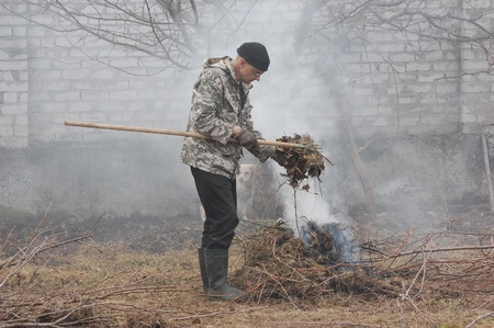 Man burn out dry grass in the garden Ukraine  photo