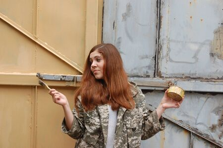 Teen girl painting old gate Ukraine photo
