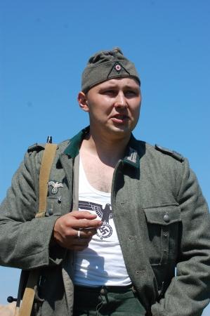 re enaction: KIEV, UKRAINE -MAY 11: Member of Red Star history club wears historical German uniform during historical reenactment of WWII, may 11, 2012 in Kiev, Ukraine  Editorial