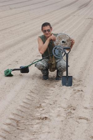 scavenge: Man with metal detector and German anti tank  landmine of WWII  Near Kiev,Ukraine Stock Photo