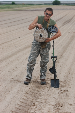 landmine: Man with metal detector and German anti tank  landmine of WWII  Near Kiev,Ukraine Stock Photo