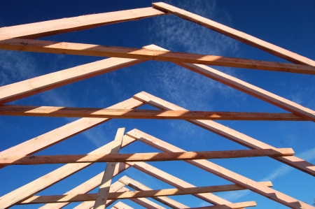 gable home renovation: Wood Roof Trusses viewed from inside of new home looking out to a blue sky above .Ukraine Stock Photo