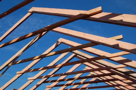 house gable: Wood Roof Trusses viewed from inside of new home looking out to a blue sky above  Ukraine