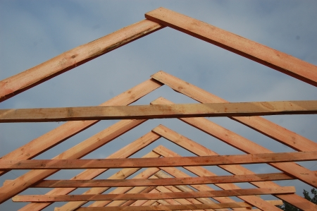 gable home renovation: Wood Roof Trusses viewed from inside of new home looking out to a blue sky above  Ukraine