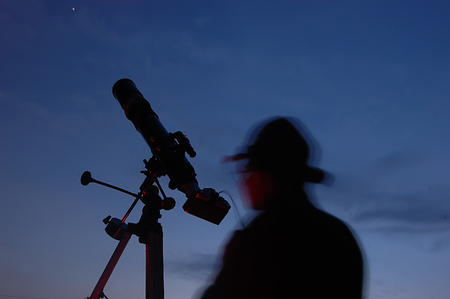 Hombre adulto y el telescopio cerca de Kiev, Ucrania