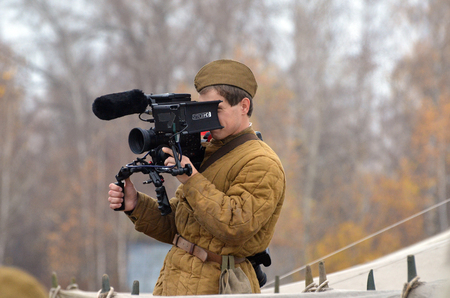KIEV, UKRAINE -NOV 3 Estonian TV cameraman wears historical Soviet uniform working during historical reenactment of WWII, Battle for Kiev 1943 on November 3, 2013 in Kiev, Ukraine