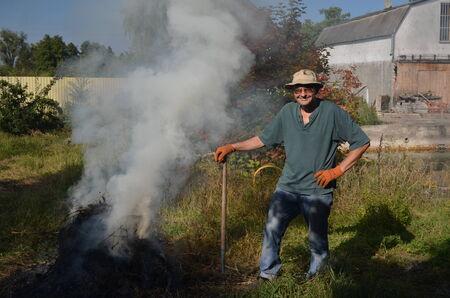 Man burn out dry grass in the garden.Ukraine photo