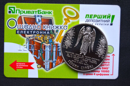 privat: Kiev,Ukraine.Dec 22.Illustrative editorial.Ukrainian commemorative coin in memory Revolution of Dignity with card of Privat Bank as background .At December 22,2014 in Kiev, Ukraine Editorial