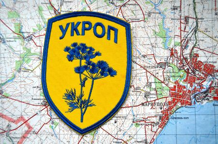 frontline: Kiev,Ukraine.JAN 10.Illustrative editorial.Unformal chevron of Ukrainian Army.With map of Mariupol. City and port on Azov Sea.At present time frontline. At January 10,2015 in Kiev, Ukraine Editorial