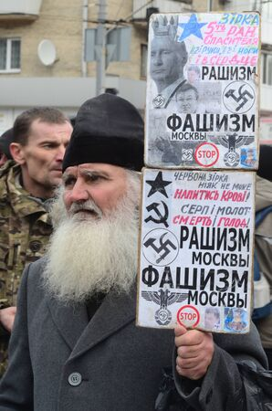"""batallon: KIEV, Ucrania - 02 de febrero 2015: Los nacionalistas ucranianos del Batall�n """"Aydar"""" queme simbol estado ucraniano durante la protesta contra el presidente Poroshenko.The puerta del Ministerio de Defensa."""