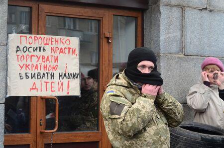 nationalists: KIEV, UKRAINE - February 2, 2015: Ukrainian nationalists of Battalion Aydar burn out ukrainian state simbol during protest against president Poroshenko.The gate of the Ministry of Defence.