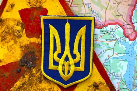 nationalist: Kiev,Ukraine.JAN 10: Chevron of Ukrainian nationalist paramilitary formation ,with sign Radioactive and Chernobyl area as background. At January 10,2015 in Kiev, Ukraine