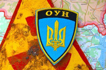nationalist: Kiev,Ukraine.JAN 10: Chevron of Ukrainian Nationalist Organisation -OUN,with sign Radioactive and Chernobyl area as background. At January 10,2015 in Kiev, Ukraine