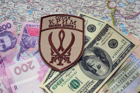 extremist: Kiev, Ukraine.NOV 13.Illustrative editorial. Chevron of Islamic extremist formation Crimea as part of Ukrainian Army.Background map and money. November 13, 2015 in Kiev, Ukraine Editorial