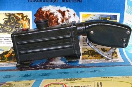 fallout: ILLUSTRATIVE EDITIRIAL.Vintage Soviet military radiometer DP-62.Background - poster Soviet Civil Defense: Atomic weapon.At April 19,2016 Kiev, Ukraine Editorial