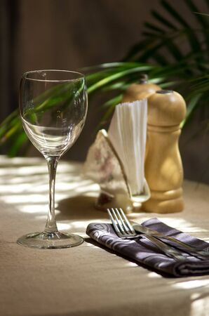 The restaurant served table for one person the sun with wine glass, cloth, paper napkins, spice and green flower Stock Photo