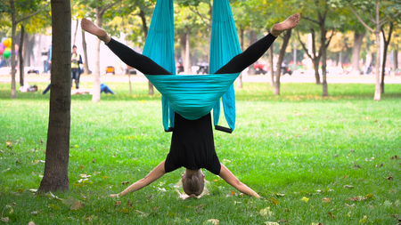 A young girl in a park engaged in aerial yoga. This type of yoga on special fabric canvases Stock Photo