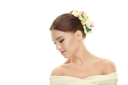 headpiece: Young adorable brunette woman with bare shoulders showing cute trendy makeup and flower headpiece posing on white studio background