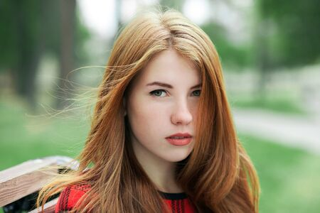 red plaid: Closeup portrait of young adorable redhead woman in red plaid jacket with blurred park background