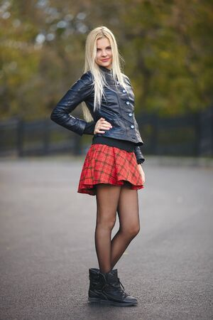 Young cute trendy dressed blonde woman having fun posing outdoors against blurry foliage background