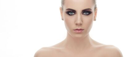 Young gloomy fashionable woman with bare shoulders and gorgeous dark smokey makeup posing on white studio background