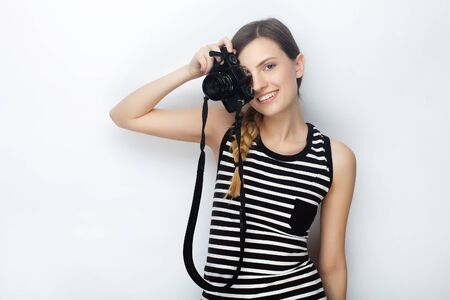 Portrait of smiling happy young beautiful woman in striped shirt posing with black photo camera against studio background