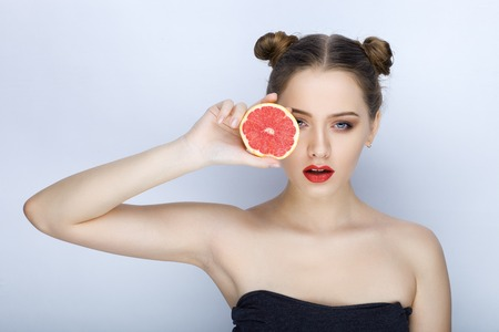 Beautiful young woman with perfect healthy skin funny hairdo trendy makeup bare shoulders holding grapefruit healthy eating organic food diet weight loss Stock Photo
