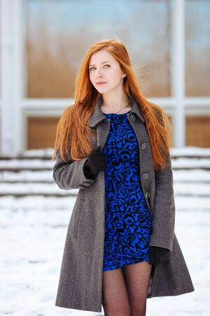 blue grey coat: Portrait of young beautiful redhead woman in blue dress and grey coat at winter outdoors